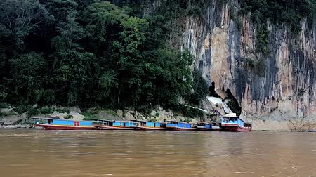 south east asia : Scene from Luang Prabang Laos South East Asia Slow PAN Motion River Shot Famous Buddhist Cave Temple Amazing Tourist