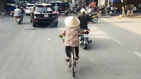 hoi an : Scene from Hanoi Vietnam Asia Slow Tracking Motion shot of Vietnamese Woman riding traditional bike wearing