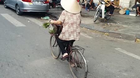 követés : Scene from Hanoi Vietnam Asia Slow Tracking Motion shot of Vietnamese Woman riding traditional bike wearing