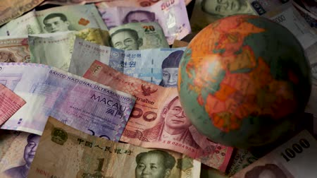 renminbi : FHD 29.97FPS footage of Foreign Currency Spinning Globe World Trade World Currency Banking Graded Stationary