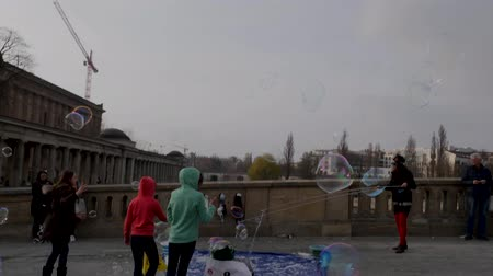 pitka : Berlin, Germany - March 23, 2019: Tourists walking over Friedrichsbrücke bridge as children play with street performers bubble display Berlin Germany