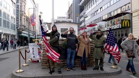cold war : Berlin, Germany - March 23, 2019: Middle Eastern  Indian Tourists posing for pictures at the Checkpoint Charlie attraction in Berlin Germany Stock Footage