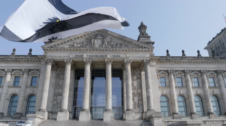 slogan : Berlin, Germany - March 23, 2019: Prussia flag flying in front of reichstag parliament building in Germanys Capitol Berlin