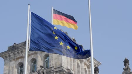 união : Berlin, Germany - March 23, 2019: The German national flag flying in the wind together with the EU flag