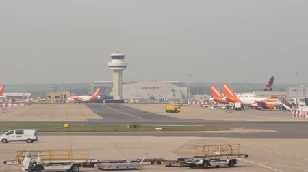 london cab : London, United Kingdom - April 19, 2019: EasyJet aircraft parked at terminal and on taxi route at London Gatwick Airport