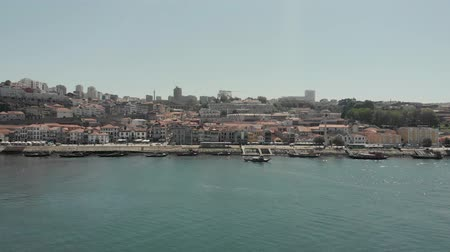 Porto, Portugal - September 1, 2019: 4k Drone Aerial flight across the river douro toward Gaia showing skyline and cityscape opposite Porto and the various port wine makers buildings. Summers day Стоковые видеозаписи