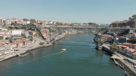 4k Drone Aerial view flying towards the Lu?s I Bridge in Porto as boat sails underneath on the river Douro. Shot in Summer on a warm day with clear blue skies Stock Footage