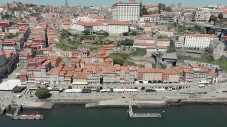4k Drone Ascent Take off Aerial view of Porto Bairro da Ribeira riverside waterfront property and boats. Views of the iconic Episcopal Palace and Bolsa Palace