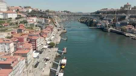 4k Drone Aerial view of Porto Bairro da Ribeira riverside waterfront property and boats. Popular place for tourists to visit with views of the iconic Lu?s I Bridge Стоковые видеозаписи