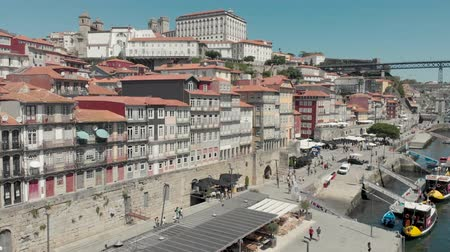 Porto, Portugal - September 1, 2019: 4k Drone Aerial view of Porto Bairro da Ribeira riverside waterfront property and boats. Popular place for tourists to visit with views of the iconic Luís I Bridge Stock Footage
