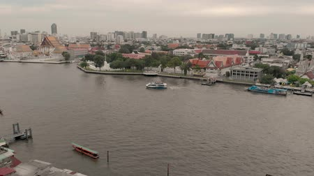 getting : Bangkok, Thailand - August 1, 2019:  4k Chao Phraya River cityscape and Wat Arun Ratchavararam, flowing through the heart of Bangkok, offers convenient boat transportation and sightseeing cruises Stock Footage