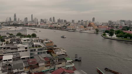 4k Chao Phraya River cityscape and Wat Arun Ratchavararam, flowing through the heart of Bangkok, offers convenient boat transportation and sightseeing cruises