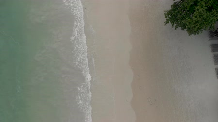 4k Aerial view Drone footage Thai Island beach with turquoise blue waves crashing against golden sands.