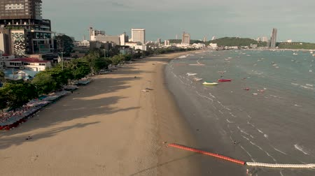 Pattaya, Thailand - August 2, 2019: 4k drone shot of Pattaya beach and beach road early morning during sunrise. Empty beach, golden sands and no people. Shows famous Pattaya City sign