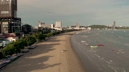 Pattaya, Thailand - August 2, 2019: 4k Drone Aerial of Pattaya Beach and famous sign. Early morning Sunrise cityscape and skyline showing golden sand beach, waves and speed boats. Chon buri Thailand