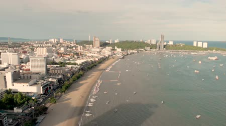 4k Drone Aerial of Pattaya Beach and famous sign. Early morning Sunrise cityscape and skyline showing golden sand beach, waves and speed boats. Chon buri Thailand