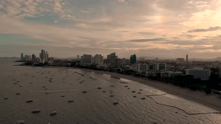 4k Drone Aerial of Pattaya Beach. Early morning Sunrise cityscape skyline. Panning shot across beach, waves, speed boats and golden sands. Beach Road Thailand
