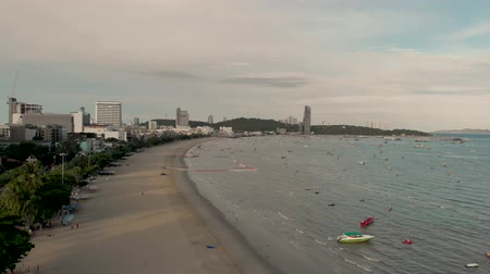 Pattaya, Thailand - August 2, 2019: 4k Drone take off. Aerial shot of Pattaya Beach and famous sign. Early morning Sunrise cityscape and skyline showing beach front properties, waves and speed boats