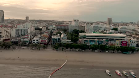 Pattaya, Thailand - August 2, 2019: 4k Drone Aerial of Pattaya Beach. Early morning Sunrise cityscape skyline. Panning shot across beach, waves, speed boats and golden sands. Beach Road Thailand Стоковые видеозаписи