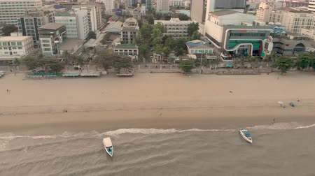Pattaya, Thailand - August 2, 2019: 4k Drone Aerial of Pattaya Beach. Early morning Sunrise cityscape skyline. Panning shot across beach, waves, speed boats and golden sands. Beach Road Thailand Stock Footage