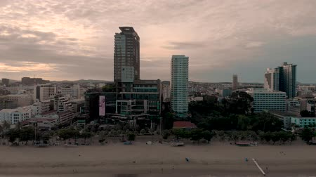 Pattaya, Thailand - August 2, 2019: 4k Drone Panning shot across Pattaya City Beach and the waterfront hotels, apartments and bars on the skyline. Early Morning Sunrise no people