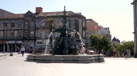 век : Lisbon, Portugal - September 5, 2019: 4k Fountain Fonte dos Leões Built in the 19th century, this octagonal Roman-style marble fountain features 4 lion statues. Tourists taking photos and exploring the square and central fountain. Стоковые видеозаписи