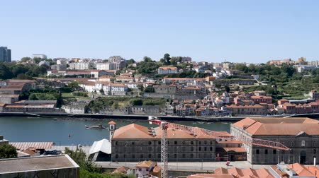 Porto, Portugal - September 5, 2019: 4k Elevated Aerial View of Porto Skyline Cityscape showing terracotta roof tops and the River Douro harbour side waterfront. Shot on a sunny day with clear blue skies. Стоковые видеозаписи