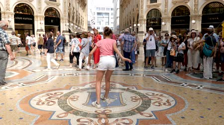 milan fashion : Milan, Italy - June 30, 2019: 4k Beautiful Young Girl Lady Woman Tourist spinning on the bulls balls mosaic in Milan tradition at the Galleria Vittorio Emanuele II arcade off the Piazza del Duomo