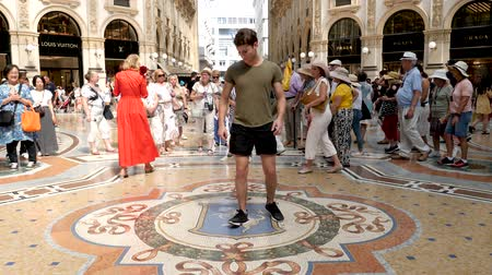 milan fashion : Milan, Italy - June 30, 2019: 4k Male Tourist spinning on the bulls balls mosaic in Milan tradition at the Galleria Vittorio Emanuele II a glass-covered 19th-century arcade off the Piazza del Duomo
