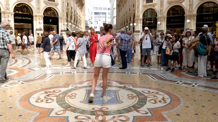 век : Milan, Italy - June 30, 2019: 4k Beautiful Young Girl Lady Woman Tourist spinning on the bulls balls mosaic in Milan tradition at the Galleria Vittorio Emanuele II arcade off the Piazza del Duomo