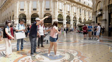 old times : Milan, Italy - June 30, 2019: 4k Asian Lady Woman Tourist spinning on the bulls balls mosaic in Milan tradition at the Galleria Vittorio Emanuele II arcade off the Piazza del Duomo