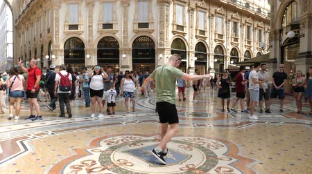 век : Milan, Italy - June 30, 2019: 4k Male Tourist spinning on the bulls balls mosaic in Milan tradition at the Galleria Vittorio Emanuele II a glass-covered 19th-century arcade off the Piazza del Duomo