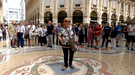 milan fashion : Milan, Italy - June 30, 2019: 4k Woman Tourist spinning on the bulls balls mosaic in Milan tradition at the Galleria Vittorio Emanuele II a glass-covered 19th-century arcade off the Piazza del Duomo Stock Footage