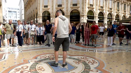 times : Milan, Italy - June 30, 2019: 4k Male Tourist spinning on the bulls balls mosaic in Milan tradition at the Galleria Vittorio Emanuele II a glass-covered 19th-century arcade off the Piazza del Duomo