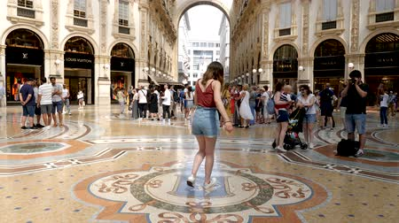 век : Milan, Italy - June 30, 2019: 4k Girl Tourist spinning on the bulls balls mosaic in Milan tradition at the Galleria Vittorio Emanuele II a glass-covered 19th-century arcade off the Piazza del Duomo