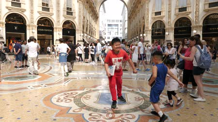 milan fashion : Milan, Italy - June 30, 2019: 4k Asian family tourists spinning on the bulls balls mosaic in Milan good luck tradition at the Galleria Vittorio Emanuele II arcade off the Piazza del Duomo Stock Footage