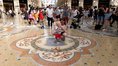 век : Milan, Italy - June 30, 2019: 4k Mother and Small Child Tourists spinning on the bulls balls mosaic in Milan tradition at the Galleria Vittorio Emanuele II an arcade off the Piazza del Duomo Стоковые видеозаписи
