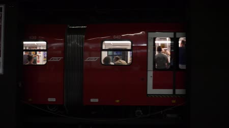 yaslanmak : Milan, Italy - June 30, 2019: 4k Slow Motion close up face on shot of Milan underground subway train leaving the platform travelling out of scene. Passengers and tourists waiting on train and platform Stok Video