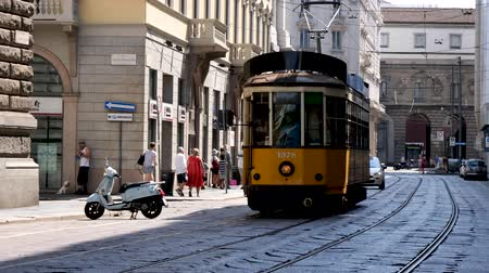 yaslanmak : Milan, Italy - June 30, 2019: 4k Milan Tram train trolley car. Clean, easy and environmentally friendly way for tourists and locals to get around the city. Classic vintage looking yellow gold car