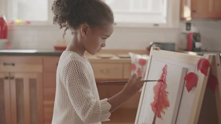 şövale : Little girl painting on a canvas Stok Video