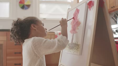 küçük kız : Little girl painting on a canvas Stok Video