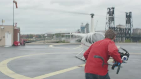Videographer running to the helicopter