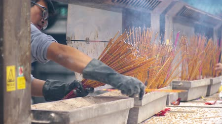 sagrado : Worker collecting temple josstick at Wong Tai Xin temple, Hong Kong