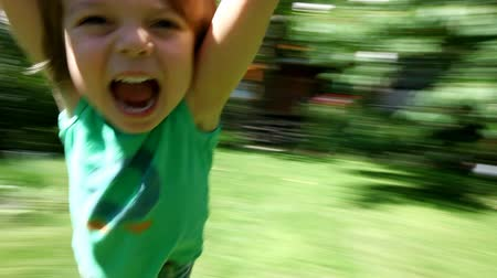 pozitivity : Little boy spinning around and around laughing and smiling at the end of his fathers arms on a sunny day