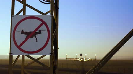 interdiction : No drone zone sign on approach lighting system at runway. Airport airspace perimeter prohibition drones fly sign. Airport infrastructure and buildings in background, against blue sky.