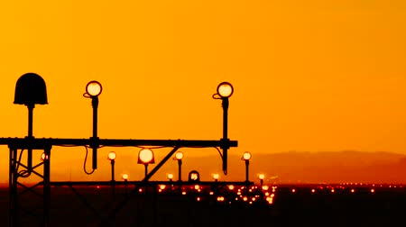 anten : Airport runway edge light indicates the landing path for planes pilots. Lights stands with four side round lamp and single big strobe in the middle. Antenna silhouettes against orange sunset backround