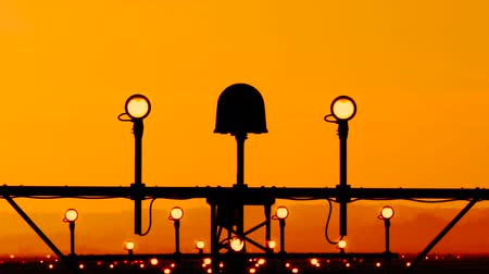 reflektör : Airport runway edge light indicates the landing path for planes pilots. Lights stands with four side round lamp and single big strobe in the middle. Antenna silhouettes against orange sunset backround