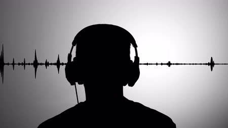 contornos : Mans black silhouette against gray wall listen to music wearing headphones, realtime waveform in background