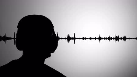 listens : Mans black silhouette against gray wall listen to music wearing headphones, realtime waveform in background