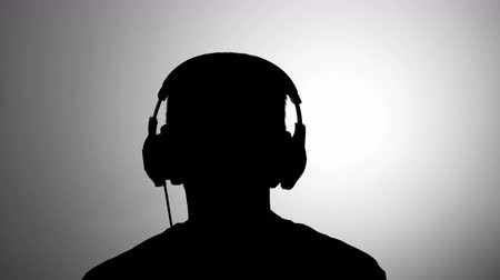contornos : Mens black silhouette against gray wall listen to music wearing headphones